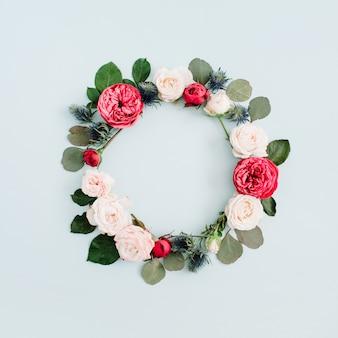Bloem frame krans gemaakt van beige en rode rozen, eucalyptus takken op bleke pastel blauwe achtergrond. platliggend, bovenaanzicht