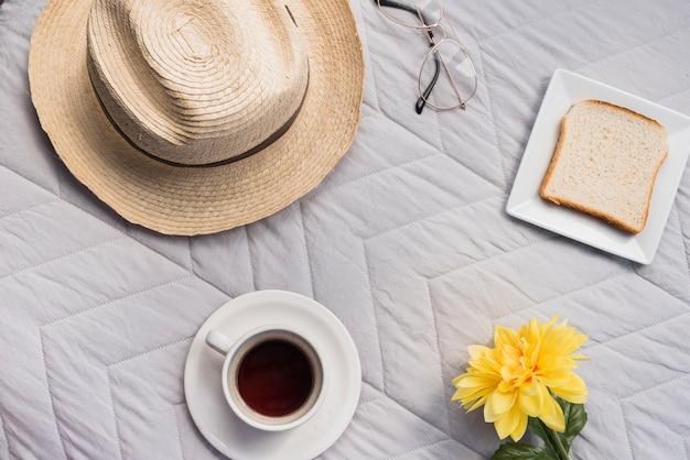 Bloem, hoed, bril, toast en een kop drinken