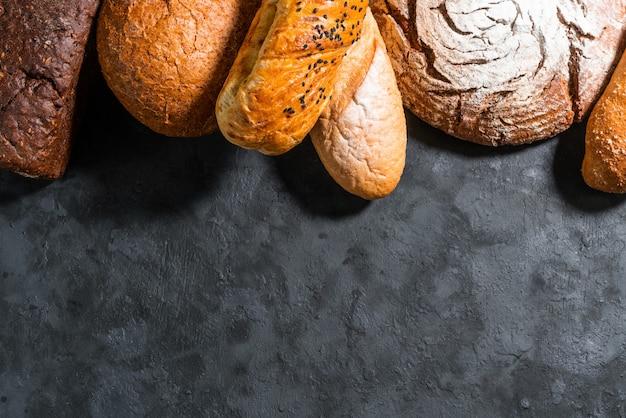 Bloem in een houten kom op donkere houten tafel met aartjes van tarwe, eieren en melk, bovenaanzicht met kopie ruimte