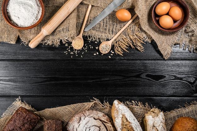 Bloem in een houten kom op donkere houten tafel met aartjes van tarwe, eieren