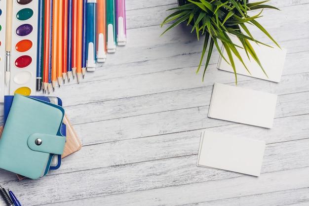 Bloem in een pot en witte visitekaartjes op een houten tafel office markers potloden verf