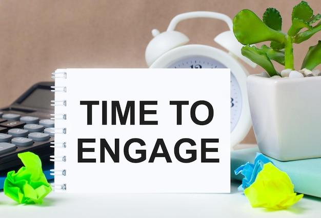 Bloem in een pot, rekenmachine, witte wekker, veelkleurige stukjes papier en een wit notitieboekje met de tekst time to engage op het bureaublad.