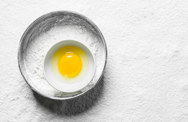 Bloem in een zeef met ei in een kom.