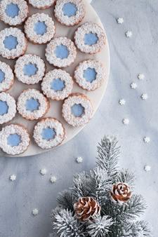 Bloem linzer-koekjes met blauw suikerglazuur op de lichte winter