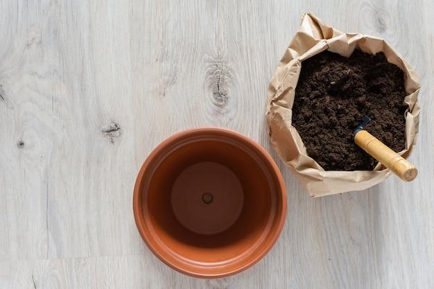 Bloem overplanten in een nieuwe bruine kleipot, de kamerplant thuis overplanten
