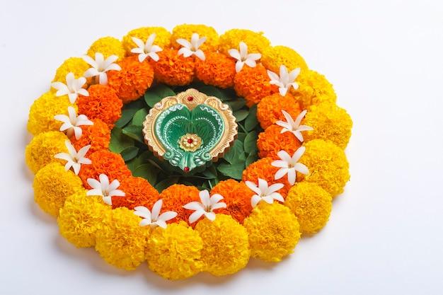 Bloem rangoli voor diwali festival gemaakt met goudsbloem en blad en olielamp op een witte achtergrond