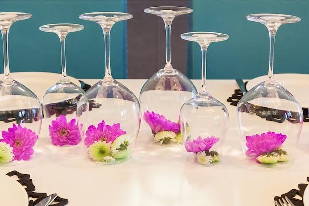 Bloem van feulette chrysant in een omgekeerd glas op tafel. decoratie van een bloem in een glas