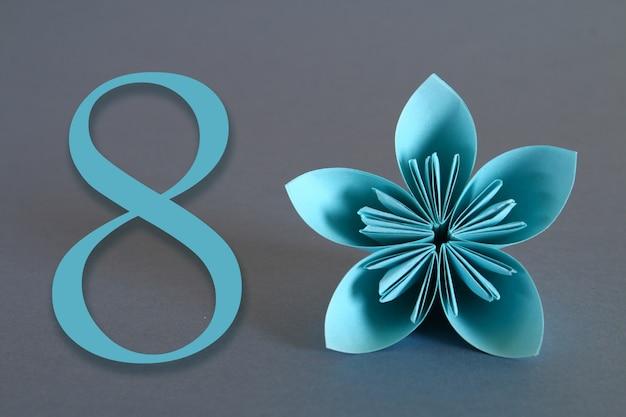 Bloem van origami met het nummer acht op een grijze achtergrond. 8 maart, internationale vrouwendag.