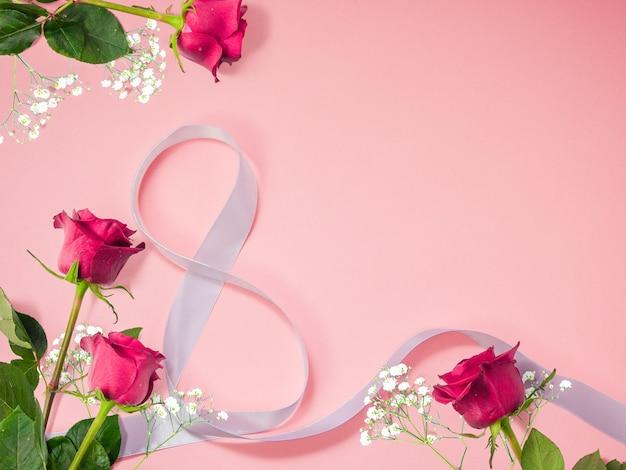 Bloemachtergrond gemaakt van rozen met decoratief wit 8-vormig lint voor de internationale vrouwendag
