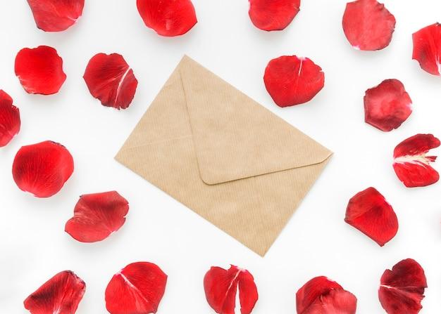 Bloemblaadjes van rode rozen met brief