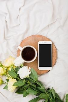 Bloemboeket met koffiekop en mobiele telefoon op bed