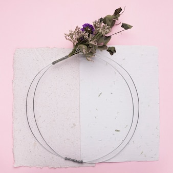 Bloemboeket op ronde ring over het papier op roze achtergrond