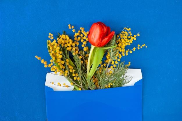 Bloemen als een geschenk in een ambachtelijke envelop in wenskaart, close-up