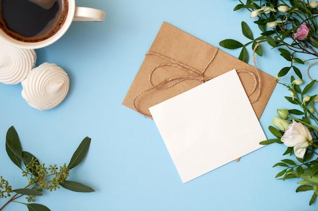 Bloemen, ambachtelijke envelop, kopje koffie op blauwe achtergrond met kopie ruimte
