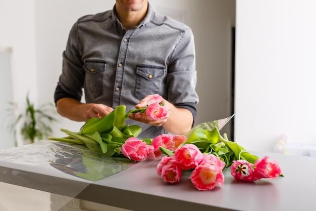 Bloemen bezorgen winkel. bloemist die orde creëert, lenteboeket maakt. mannen maken boeket met tulpen