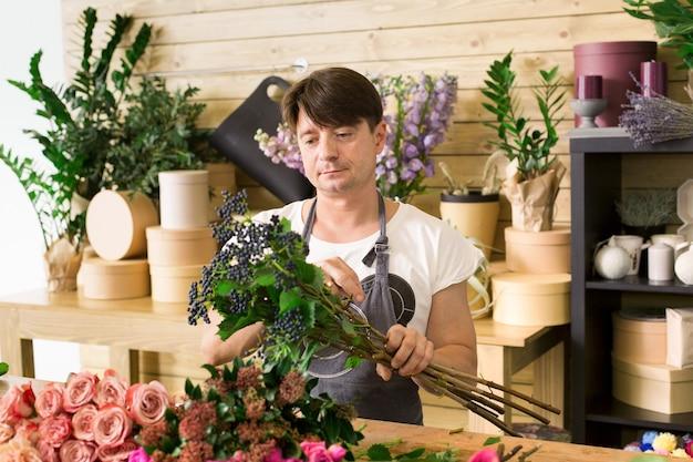Bloemen bezorger. mannelijke bloemist rozen boeket maken. man assistent of eigenaar in bloemenwinkel, decoraties en arrangementen maken. orde scheppen