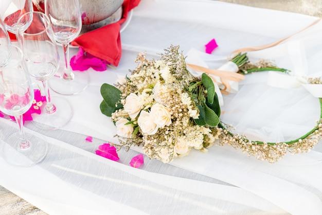 Bloemen boeket en glas en champagne in huwelijksboog