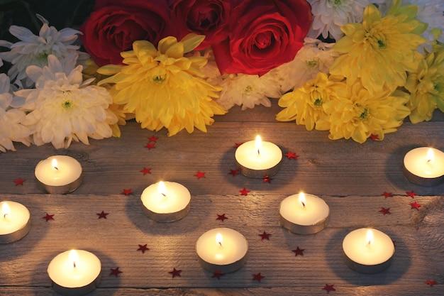 Bloemen, confetti en kaarsen op een houten platform, bovenaanzicht.