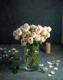 Bloemen decor lichtroze rozen in vaas schaar touw en rozenblaadjes op zwart