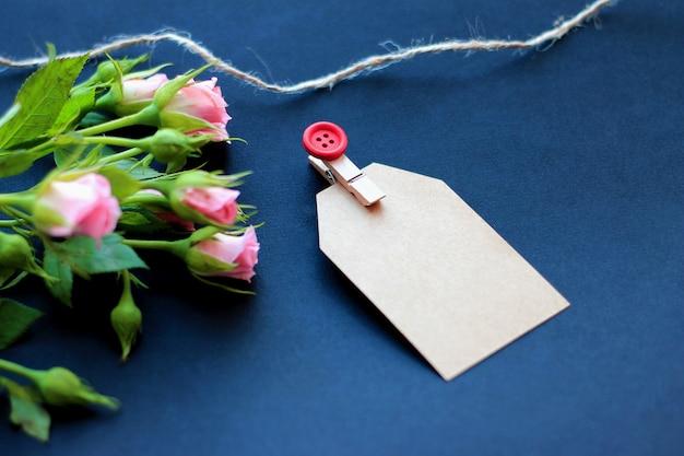 Bloemen, decoratieve wasknijpers en papier voor notities op een donkere achtergrond. concept gefeliciteerd met de vakantie