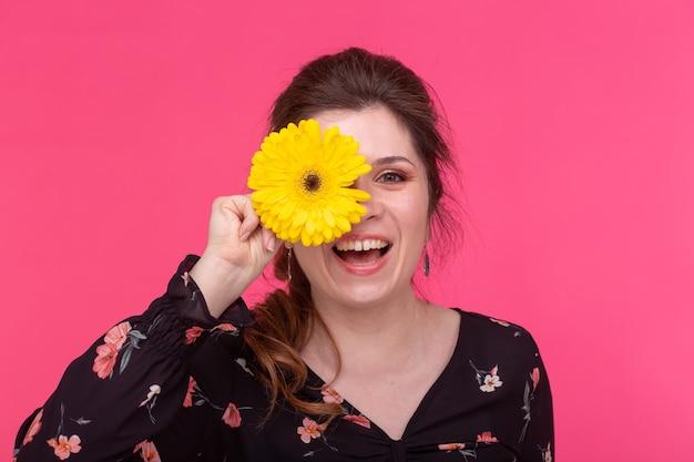 Bloemen, emoties en mensenconcept - vrouw sloot haar oog met gerbera op roze achtergrond