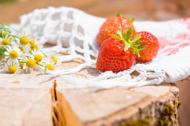 Bloemen en aardbeien op een oud houten logboek.