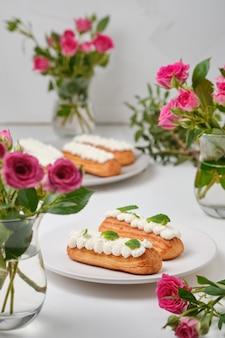 Bloemen en eclairs versierd met room en munt op een witte tafel. dessert voor een romantische date. taarten voor de vakantie.
