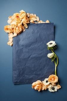 Bloemen en een stuk zwart papier in een frame met ruimte voor tekst op een donkere achtergrond, plat gelegd