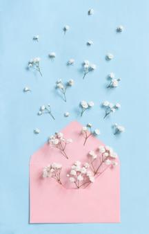 Bloemen en envelop op een lichtblauwe bovenaanzicht als achtergrond