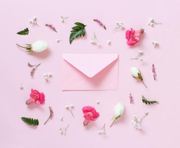 Bloemen en envelop op een lichtroze bovenaanzicht als achtergrond