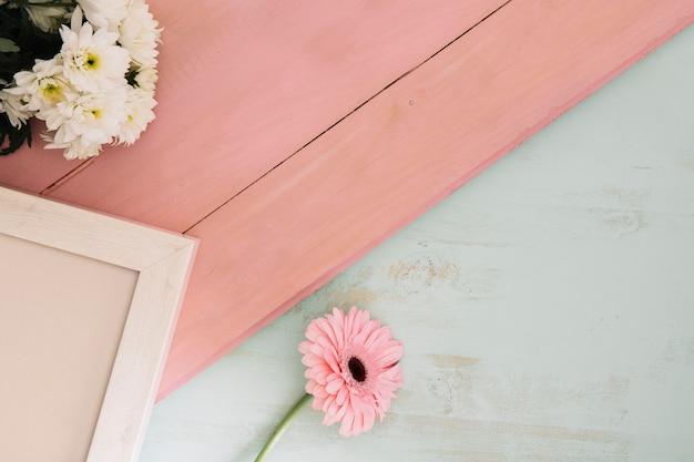 Bloemen en frame op roze oppervlak