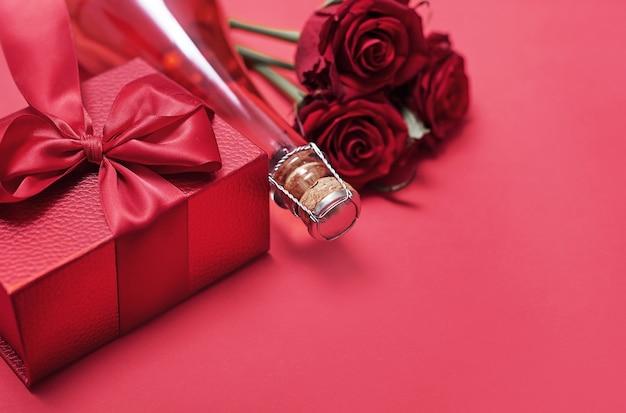 Bloemen en geschenkdozen op rode champagnefles en glazen
