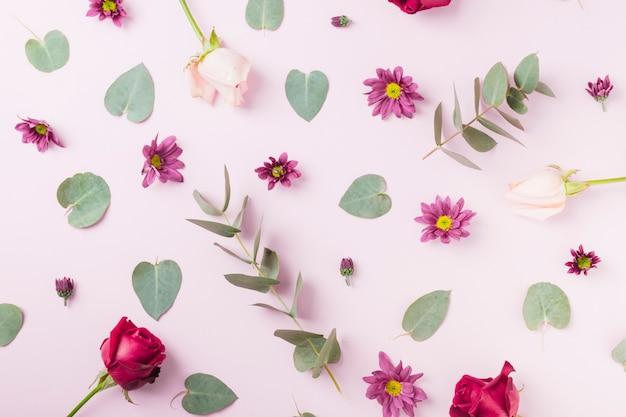 Bloemen en groene bladeren op roze achtergrond