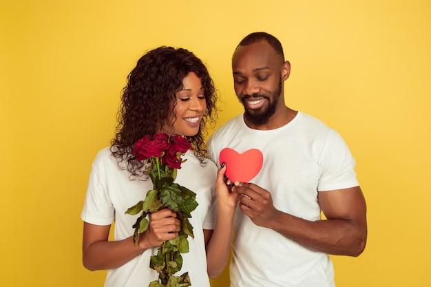 Bloemen en hart. valentijnsdagviering, gelukkig afrikaans-amerikaans paar dat op gele studioachtergrond wordt geïsoleerd. concept van menselijke emoties, gezichtsuitdrukking, liefde, relaties, romantische vakanties.