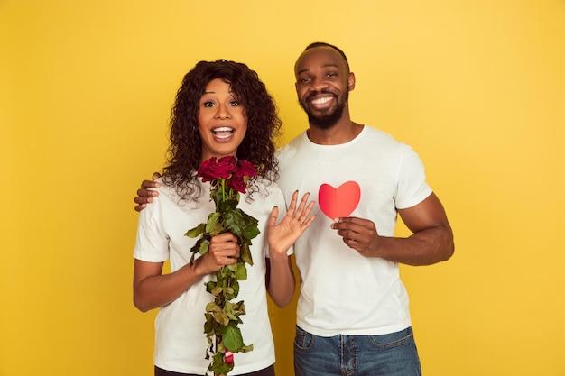 Bloemen en hart. valentijnsdagviering, gelukkig afrikaans-amerikaans paar dat op gele studioachtergrond wordt geïsoleerd.
