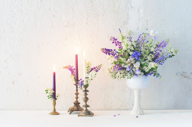 Bloemen en kaarsen op witte muur als achtergrond