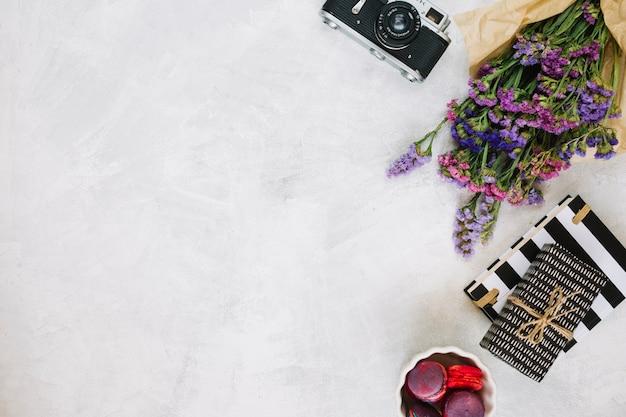 Bloemen en retro camera in de buurt van geschenken en bitterkoekjes