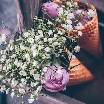 Bloemen en roze roos in wafel kegel in houten kist