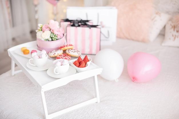 Bloemen en snoep op witte tafel en ballonnen op het witte bed. cadeau voor moederdag