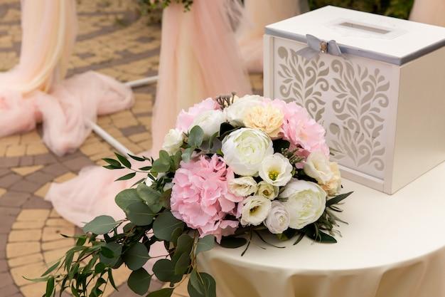 Bloemen en vak voor geld op tafel