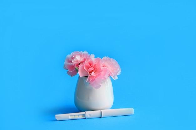 Bloemen en zwangerschapstest op een blauwe achtergrond