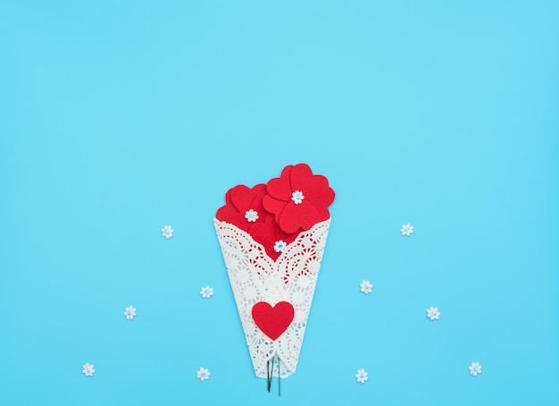 Bloemen gemaakt van vilten harten gewikkeld in een witte kanten bundel op blauwe achtergrond met kleine witte bloemen.