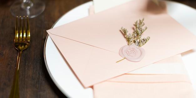 Bloemen gestempelde roze envelop op een bord