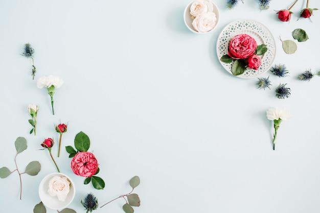 Bloemen grenskader gemaakt van rode en beige rozen, witte anjer en eucalyptus takken op bleke pastel blauwe achtergrond. platliggend, bovenaanzicht