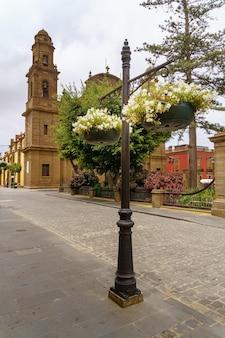 Bloemen hangen in manden in een straat in de stad galdar op gran canaria. europa,