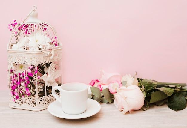 Bloemen in antieke kooi; kop; schotel en rozen op houten tafel tegen roze achtergrond