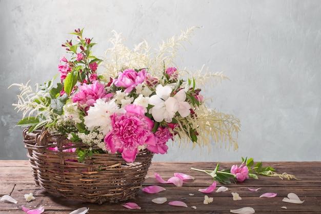 Bloemen in de mand op oude houten tafel