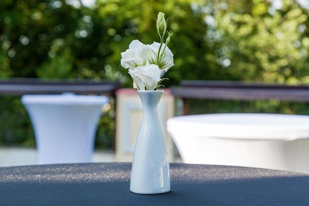 Bloemen in de vaas op tafel, decor voor het evenement