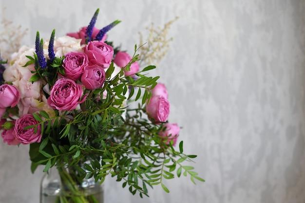 Bloemen in een glazen pot op grijze betonnen achtergrond. vintage woondecoratie. kopieer ruimte voor tekst.