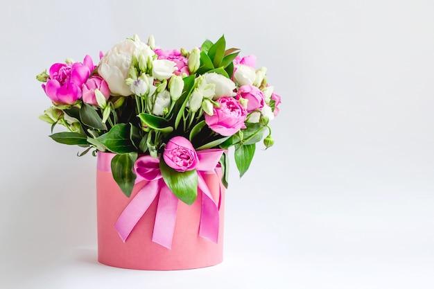 Bloemen in een hoedendoos. boeket van roze en witte pioenen, eustoma, nevelroos in een roze doos
